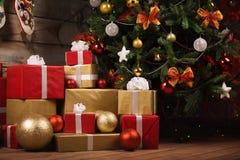 礼物盒和球在圣诞树下 库存照片