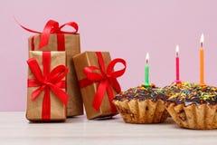 礼物盒和生日杯形蛋糕与烧欢乐蜡烛在桃红色背景 库存图片