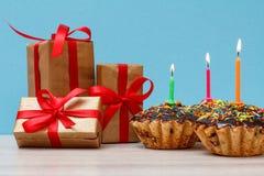 礼物盒和生日杯形蛋糕与烧欢乐蜡烛在蓝色背景 库存照片