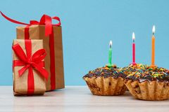 礼物盒和生日杯形蛋糕与烧欢乐蜡烛在蓝色背景 免版税库存照片
