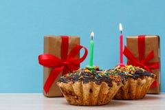 礼物盒和生日杯形蛋糕与烧欢乐蜡烛 图库摄影