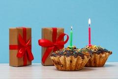 礼物盒和生日杯形蛋糕与烧欢乐蜡烛 库存图片
