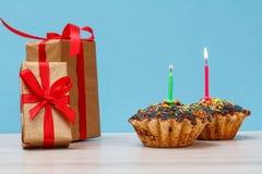 礼物盒和生日杯形蛋糕与烧欢乐蜡烛 库存照片