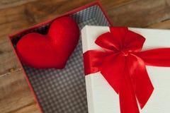 礼物盒和红色丝带和微型心脏里面在木头后面 库存照片