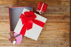 礼物盒和红色丝带和微型心脏里面在木头后面 免版税库存图片