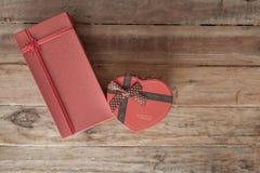 礼物盒和红色丝带和微型心脏里面在木backgr 免版税库存照片