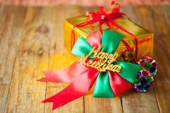 礼物盒和红色丝带和新年好礼物在木头b 免版税库存照片