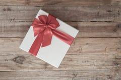 礼物盒和红色丝带在木背景与空间 库存图片