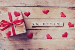礼物盒和红色心脏与木文本华伦泰在木桌上 图库摄影