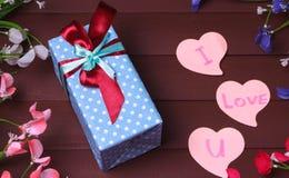 礼物盒和红色心脏与木文本我爱你木桌背景的 库存图片