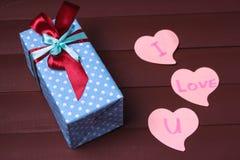 礼物盒和红色心脏与木文本我爱你木桌背景的 免版税库存图片