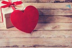 礼物盒和红色心脏在木桌上与空间 免版税库存照片