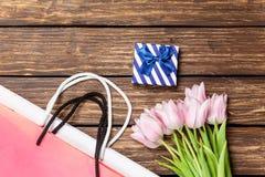 礼物盒和袋子与花束ofr郁金香 免版税库存照片