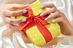 礼物盒在女性被修剪的手上 库存照片