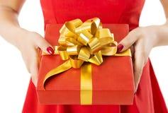 礼物盒提出与丝带和弓,拿着红色礼物的妇女 免版税库存照片