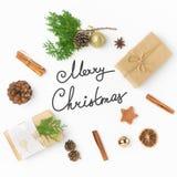 礼物盒杉木锥体杜松桂香装饰品球在白色的圈子安排了 圣诞快乐字法 免版税库存图片