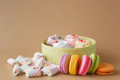 礼物盒杯形蛋糕和五颜六色的Macaron在米黄背景, 库存图片