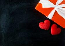 礼物盒白色弓丝带和红色心脏在黑板制表背景 库存照片