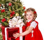 给礼物盒的孩子由圣诞树。 免版税图库摄影