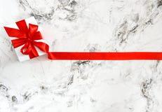 礼物盒红色丝带弓大理石背景 免版税库存图片