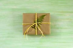 礼物盒被包裹工艺纸和白色和黄色丝带与蕨叶子在绿色木背景 库存图片