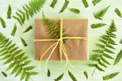 礼物盒被包裹工艺纸和白色和黄色丝带在绿色木背景装饰蕨叶子 库存照片