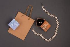 礼物袋子,在圆点的礼物盒与在灰色ba的珍珠首饰 免版税库存图片