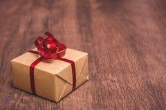 礼物,栓与一条红色丝带和包裹在木背景的牛皮纸 免版税库存图片