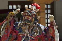 礼节古老面具妖怪和典雅的狂欢节衣物的和尚有一块头骨的在他的手上执行可汗舞蹈我 免版税库存照片