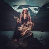 礼节服装的北欧女神与在狂放的山湖附近的鹰Innerdalen谷的 库存图片
