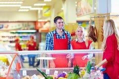 礼貌的杂货职员为购物中心的顾客服务 库存图片