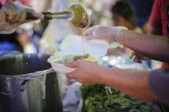 社会不平等的概念:捐赠食物对叫化子缓和饥饿:贫寒的手从接受食物 免版税库存图片