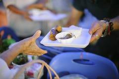 社会不平等的概念:捐赠食物对叫化子缓和饥饿:贫寒的手从接受食物 图库摄影