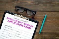 社会保险津贴 在笔附近的在黑暗的木背景顶视图拷贝空间的申请表和玻璃 库存图片