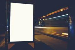 社会信息委员会与被弄脏的夜在背景点燃,给嘲笑做广告在外面,在路旁的空白的海报 库存图片