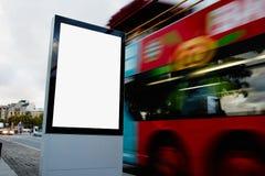 社会信息委员会在有有被弄脏的公共汽车的城市在背景,横幅的空的广告嘲笑在车行道 免版税图库摄影