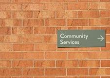 社区服务在红砖墙壁上签字 免版税库存图片