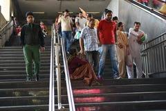 社论:古尔冈,德里,印度:2015年6月07th日:一名未认出的老可怜的妇女乞求从人在古尔冈地铁站乐团 免版税库存照片