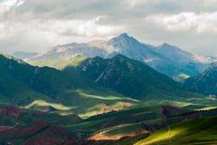 祁连山,青海,中国,下午太阳通过云彩照亮山 库存照片