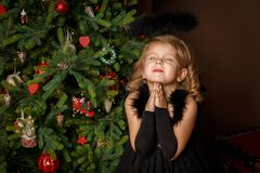 祈祷一套黑天使服装的一个小女孩,看充满希望为和平 愉快的童年和和平 圣诞节新年度 库存图片