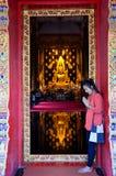 祈祷与反射金黄菩萨雕象的泰国妇女 免版税库存照片