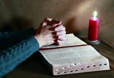 祈祷与圣经和灼烧的蜡烛 免版税库存照片