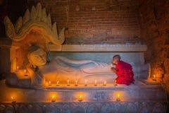 祈祷与在Buddihis的蜡烛光的东南亚初学者 库存图片
