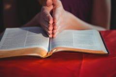 祈祷与她的圣经的妇女 免版税库存照片