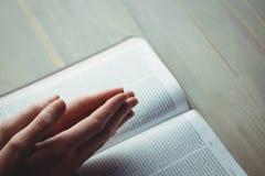 祈祷与她的圣经的妇女 图库摄影