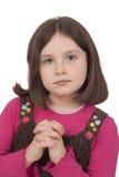 祈祷与开放眼睛的美丽的女孩 免版税库存图片