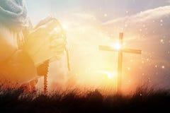 祈祷与念珠胡子和十字架的妇女在自然日落 库存照片