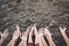 祈祷为在破裂的干燥地面的雨的孩子的脚和手 库存图片