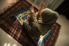 祈祷为阿拉回教神的回教妇女在室在窗口附近 地毯的祈祷在传统佩带的回教妇女的手 免版税库存图片