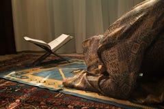 祈祷为阿拉回教神的回教妇女在室在窗口附近 地毯的祈祷在传统佩带的回教妇女的手 图库摄影